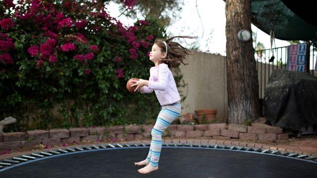 Fille jouant au basket sur un trampoline